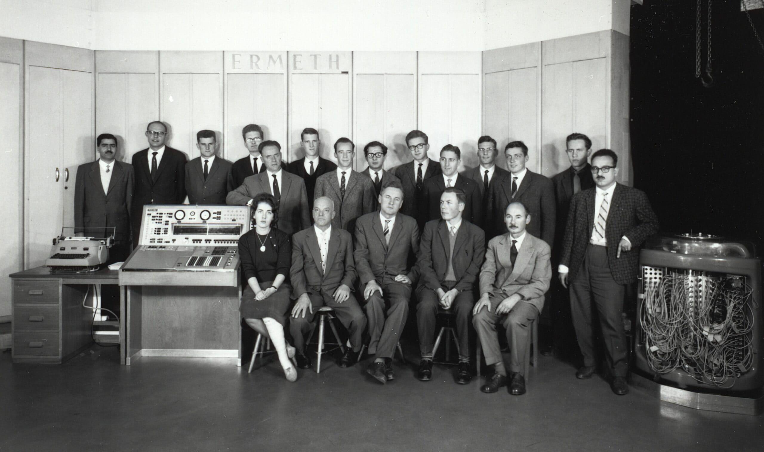 Die Crew des Institut für angewandte Mathematik posiert vor der ERMETH, 1963. Stehend von links: Boutros, Gantenbein, Stofer, Siklossy, Stiefel, Rössler, Waldvogel, Koutroufiotis, Szigeti, Schwarz, Schai, Zehnder, Ganz, Amer; sitzend von links: Meier, Schär, Rutishauser, Läuchli, Amman. Rechts im Bild der durchzugempfindliche Trommelspeicher. Quelle: Bildarchiv ETH-Bibliothek, Zürich.